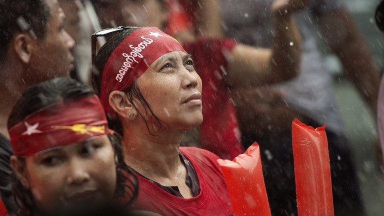 Supporters of Myanmar opposition leader Aung San Suu Kyi brave the rain as they celebrate after hearing the first official results of the elections (AFP PHOTO / Nicolas ASFOURI).