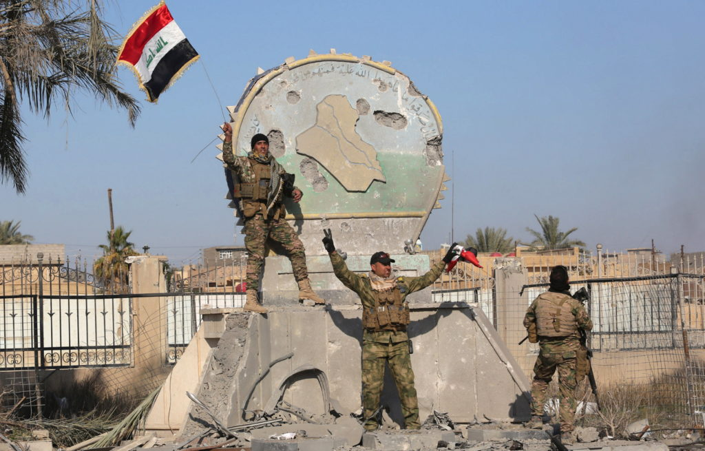 A member of the Iraqi security forces holds an Iraqi flag at a government complex in the city of Ramadi, December 28, 2015. REUTERS/Stringer EDITORIAL USE ONLY. NO RESALES. NO ARCHIVE - RTX20BBF