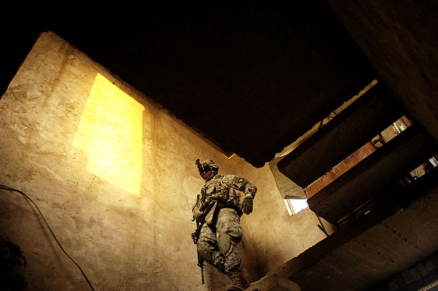 U.S. Army 1st Sgt. Eric Davis comes down a flight of stairs after clearing the upstairs portion of an abandoned home in Fair al Jair, Iraq, on Dec. 16, 2007. Davis and his fellow soldiers from the 3rd Battalion, 187th Infantry Regiment, 3rd Brigade Combat Team, 101st Airborne Division, are searching for al-Qaeda insurgents in Fair al Jair.