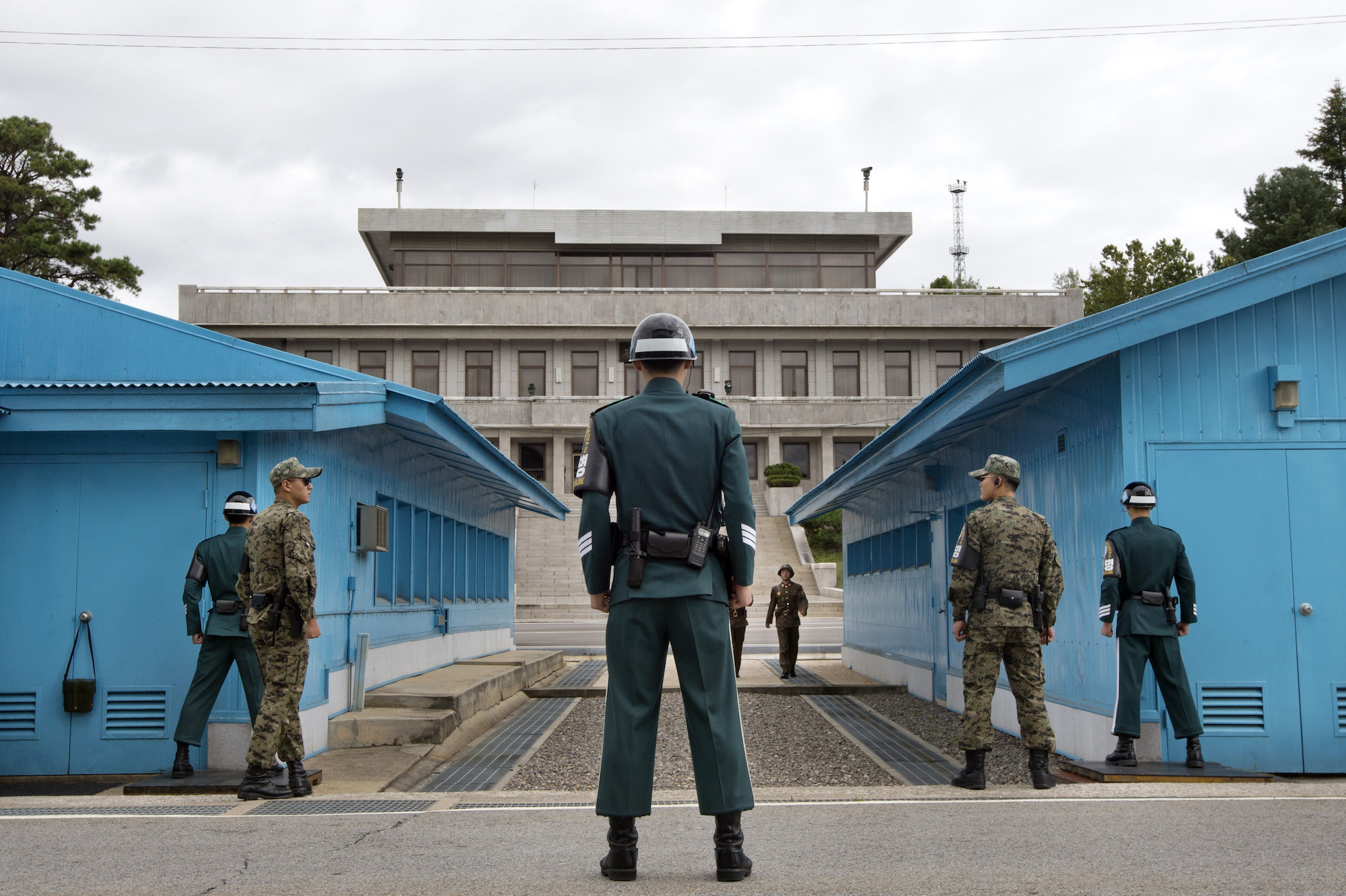 South Korean soldiers look toward the North Korean side as a North Korean solder approaches the UN truce village building that sits on the border of the Demilitarized Zone (DMZ), the military border separating the two Koreas, during the visit of U.S. Secretary of Defense Chuck Hagel to the DMZ in Panmunjom, South Korea, on Monday, Sept. 30, 2013. (AP Photo/Jacquelyn Martin, Pool)
