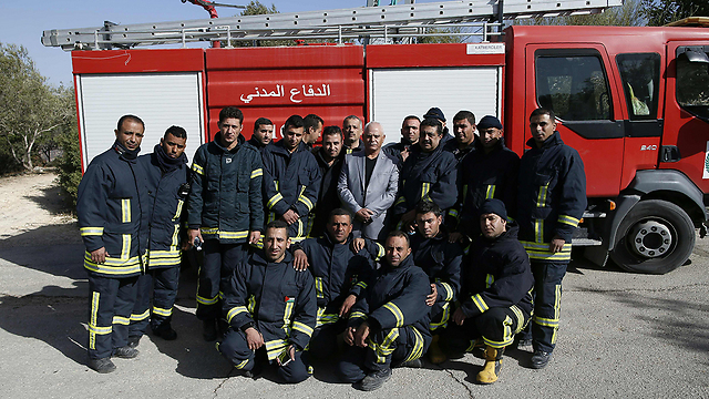 Palestinian firefighters after helping to extinguish the Nahf fire. (Agence France Presse)