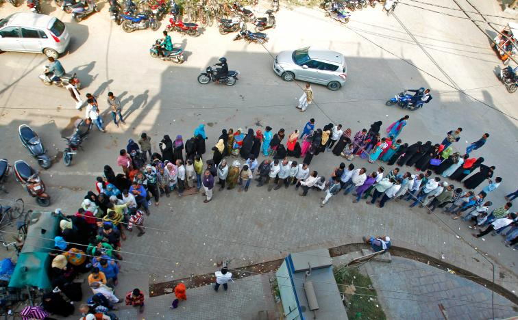 Customers wait in an exceptionally long line outside a bank in Allahabad, India on Nov. 16, 2016. Indian PM Narendra Modi turned the country's economy upside down by banning its 2 most common bank notes. Photo: Reuters/Jitendra Prakash