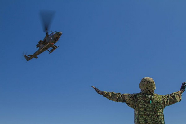 A Japan Ground Self-Defense Force member guides a Cobra anti-tank helicopter onto a forward aircraft refueling point at Yakima Training Center, Wash., Sept. 4. The exercise was part of Operation Rising Thunder, a combined operation between the Army and Japan designed to increase interoperability between the two nations. (U.S. Army photo by Sgt. Cody Quinn, 28th Public Affairs Detachment)