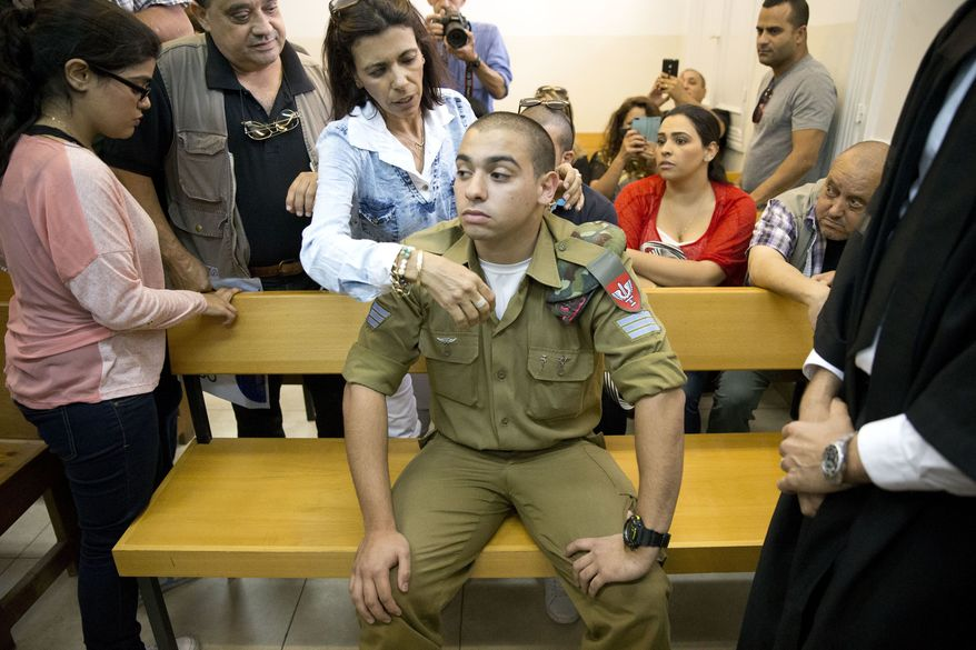 Sgt. Elor Azaria sits surrounded by family in an Israeli military court in Tel Aviv. (AP Photo)