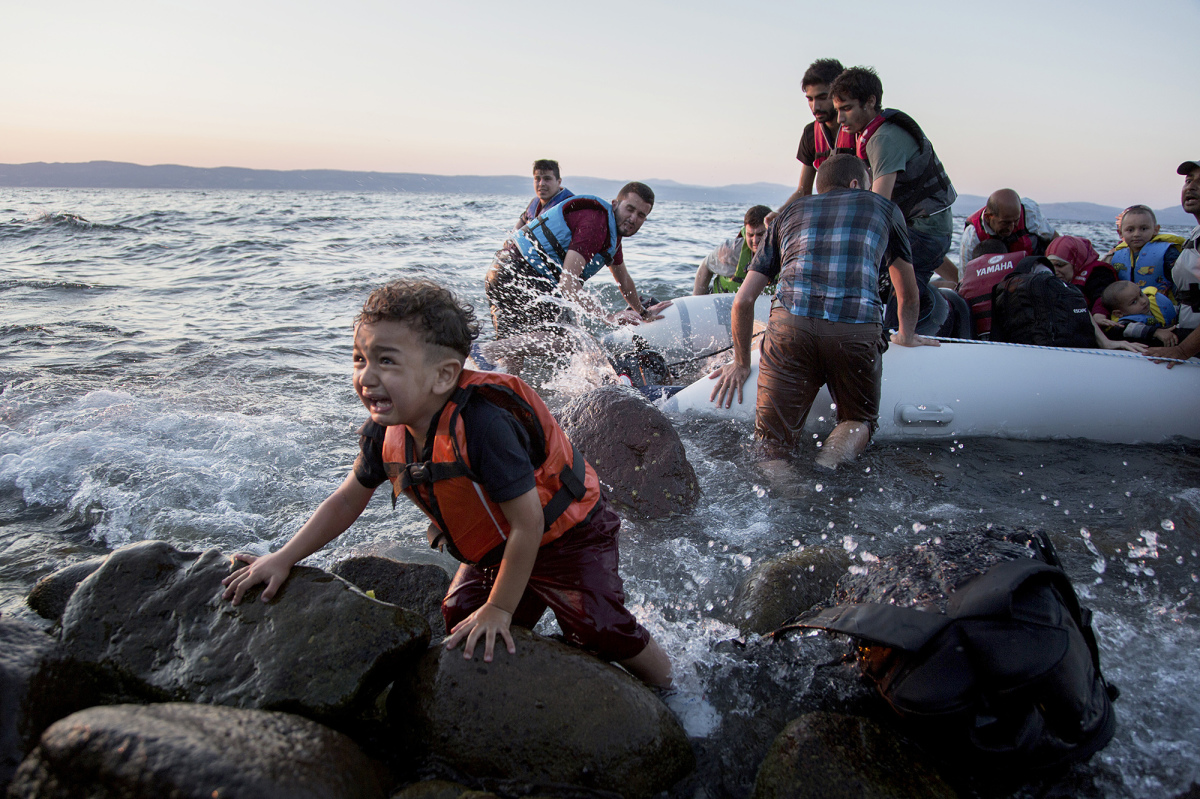 A group of Syrians arrives on Lesvos after sailing on an inflatable raft from Turkey. (ANDREW MCCONNELL / PANOS)