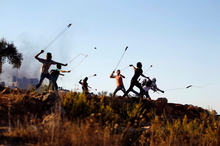 Palestinian protesters hurl rocks at Israeli soldiers during clashes in Betunia, near the West Bank city of Ramallah October 11, 2013. REUTERS/Mohamad Torokman (WEST BANK - Tags: POLITICS CIVIL UNREST TPX IMAGES OF THE DAY)