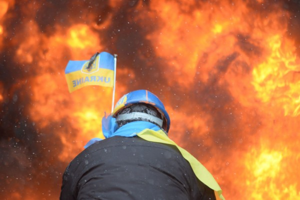 Protester_wearing_Ukraine_state_flag_colors_facing_the_massive_fire_set_by_protesters_to_prevent_internal_forces_from_crossing_the_barricade_line._Kyiv,_Ukraine._Jan_22,_2014