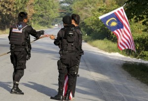 A Malaysian flag is removed by security forces in southern Thailand.