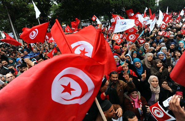 Tunisians observe the third anniversary of the end of totalitarian rule, in January 2014. While much progress has been made toward becoming a true democracy, many challenges still lie ahead. Photo: Fethi Belaid/Agence France-Presse — Getty Images