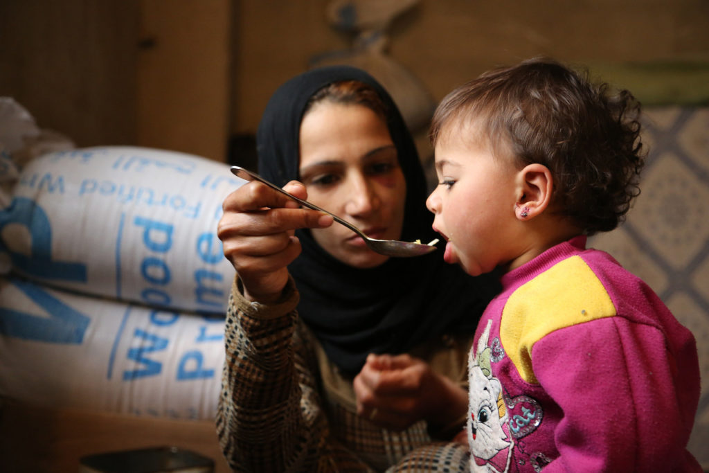 Syria, Al Tanaya village Adra (rural Damascus), 3 December 2013 Fatema, 24 years old - displaced with her family from Douma in rural Damascus to Adra - feeding her 18 month old daughter Haneen lunch. Photo: WFP/Abeer Etefa
