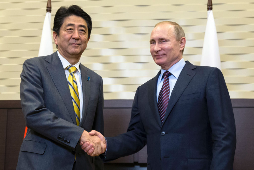 Russian President Vladimir Putin (R) shakes hands with Japanese Prime Minister Shinzo Abe during a meeting at the Bocharov Ruchei state residence in Sochi on May 6, 2016. / AFP PHOTO / POOL / Pavel Golovkin