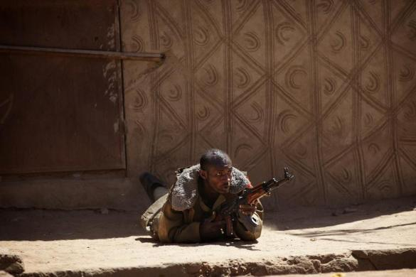 A Malian soldier fires an AK-47 during fighting with Islamists in Gao, Mali, February 21, 2013.  [REUTERS/Joe Penney]