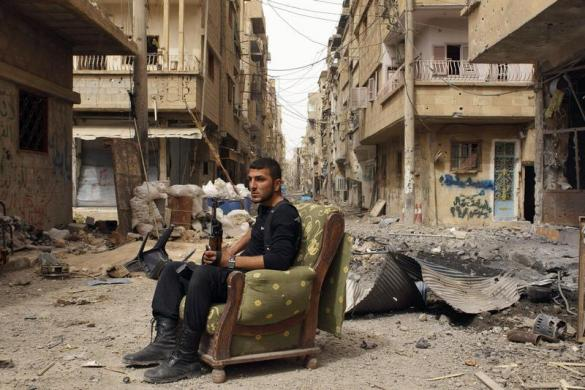 A member of the Free Syrian Army holds his weapon as he sits on a sofa in the middle of a street in Deir al-Zor April 2, 2013.  REUTERS/Khalil Ashawi