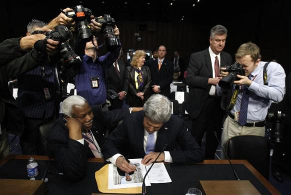 U.S. Senator John Kerry signs an autograph for Senate Foreign Relations Committee staff member Bertie Bowman after Kerry's confirmation hearing to be Secretary of State. [Reuters/Gary ]