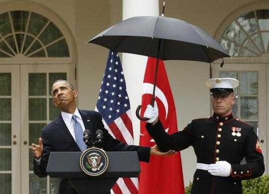 U.S. President Barack Obama checks to see if he still needs the umbrella held by a U.S. Marine to protect him from the rain during a joint news conference with Turkish Prime Minister Recep Tayyip Erdogan in the Rose Garden of the White House in Washington, May 16, 2013.  REUTERS/Jason Reed