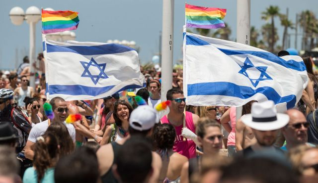 Participants wave Israeli's flags during the 2014 annual gay pride parade in Tel Aviv. (AFP)