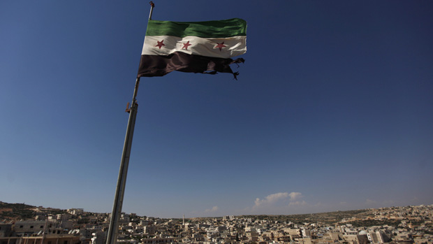 A Syrian revolutionary flag flies above buildings on the outskirts of Aleppo. (Khalil Hamra/Associated Press)