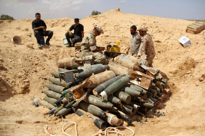 Libyan militia watch over explosives and shells left behind by Islamic State soldiers in the battle over the city of Surt, Libya on Sept. 9, 2016. Photo: REUTERS/Stringer