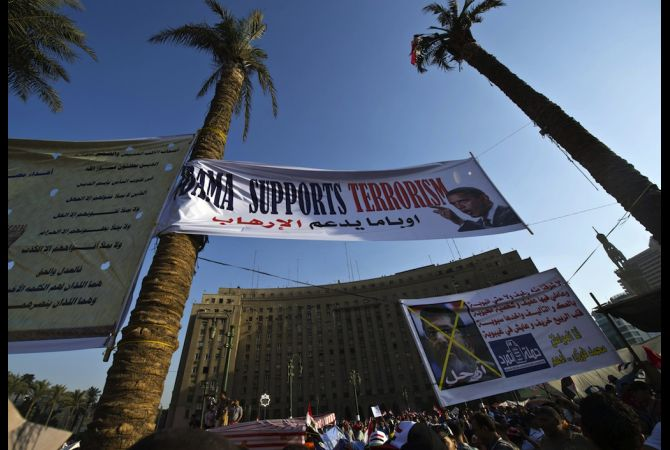 A sign denouncing US President Barack Obama and his supposed support of deposed Egyptian leader Mohamed Morsi hangs above protesters in Cairo, Egypt on June 30, 2013. Photo: KHALED DESOUKI/AFP/Getty Images