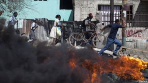 People pass a burning barricade during protests in Croix des Bouquets on the outskirts of Port-au-Prince, Feb. 2, 2015 [credit: Reuters]