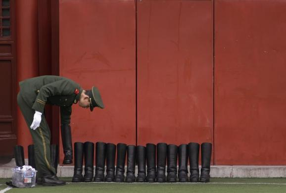 A paramilitary police officer lines up a row of newly-polished soldiers' boots during the week-long Chinese New Year holiday at the Forbidden City compound in Beijing February 14, 2013. REUTERS/Petar Kujundzic