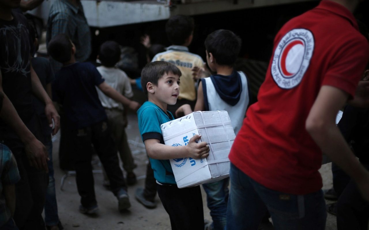 A Syrian boy helps unload supplies from a U.N. convey in Harasta, Syria--a rebel-controlled suburb of Damascus--in May 2016. The U.N. recently sent supplies to Haraya, Syria for the first time in over 4 years. Photo: ABDULMONAM EASSA/AFP/GETTY IMAGES